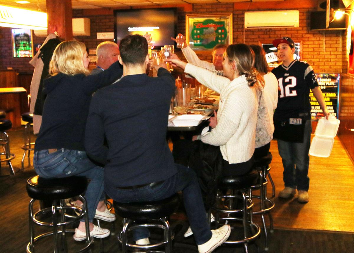 Football fans gathered at C.C. O'Brien's Pub in Pawcatuck Sunday, February 3rd, 2019, to watch the New England Patriots play the Los Angeles Rams in Super Bowl LIII. These friends raise a glass to toast good times, good fun, and the game. | Jackie L. Turner, Special to The Sun.