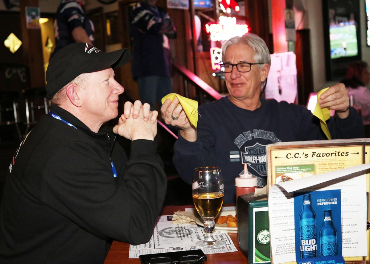 Local football fans Jack Hughes (left) and Tom Carver (right) have a beer and a bite to eat while watching Super Bowl LIII at C.C. O'Brien's Pub in Pawcatuck Sunday, February 3rd, 2019. The two guys want to be sure everyone knows they are also big Harley-Davidson fans! | Jackie L. Turner, Special to The Sun.