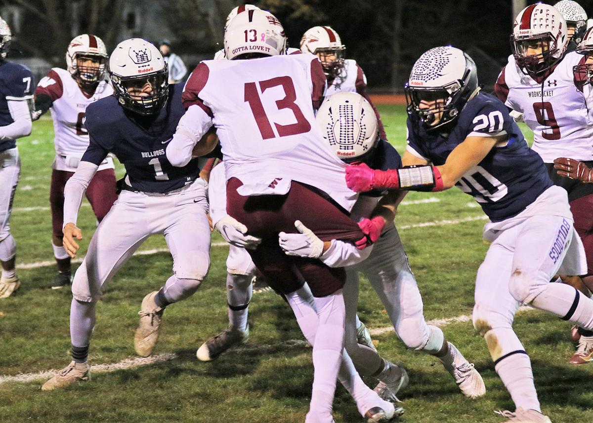 Westerly teammates Luke Marley (1), Nick Lauzon (14), and Aron Perez (20) take down Woonsocket's Eric Agyemang in the Westerly vs Woonsocket boys' varsity football DIV-II playoff game on Friday evening, November 8th, 2019, at Westerly High School's Augeri Field, Westerly, RI.   Jackie L. Turner, Special to The Sun.