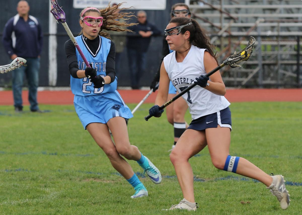 Kata Cummings (7) rushes the ball upfield for Westerly against the defense of Johnston's Bianca Robbins (23) in the Westerly vs Johnston Division-II girls' varsity lacrosse game played Wednesday afternoon, May 29th, 2019 at Westerly High School's Augeri Field. Westerly came away with the win 13-4 against Johnston. Jackie L. Turner, Special to The Sun.