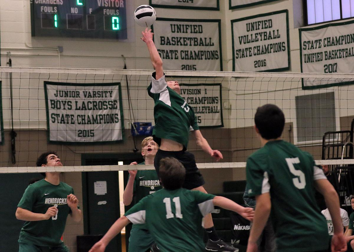 Tom Hingerty (13) tips the ball over for Chariho while teammates Riley Hughes (11) and Connor Allamby (5) look on. The Chariho High School Boys Varsity Volleyball team hosted Bishop Hendricken on Thursday evening, April 4th, 2019 at Chariho High School. | Jackie L. Turner, Special to The Sun.