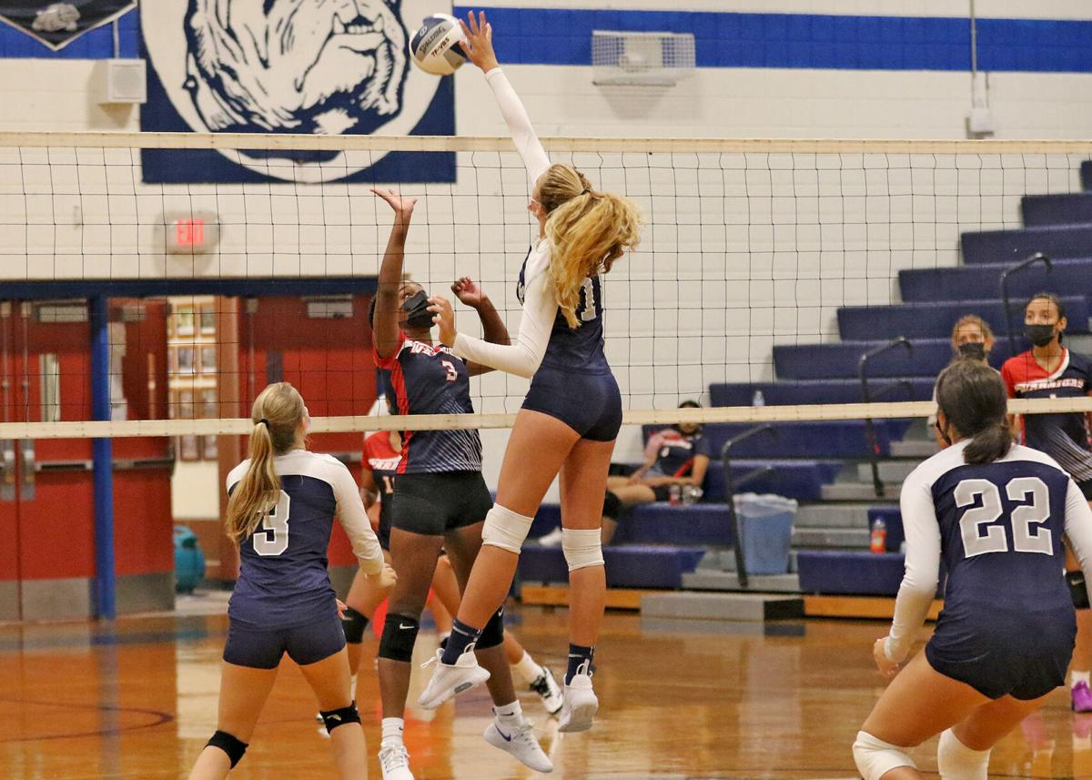 Westerly's Riley Peloquin (16) taps the ball across the net for the Bulldogs while teammate Sara Ridler (3) looks on in the second set of the Westerly Bulldogs vs Central Falls Warriors girls varsity volleyball game played Thursday evening, September 9, 2021 at Westerly High School. Central Falls senior Amayah Bell (3) defends for the Warriors.   Jackie L. Turner, Special to the Sun.