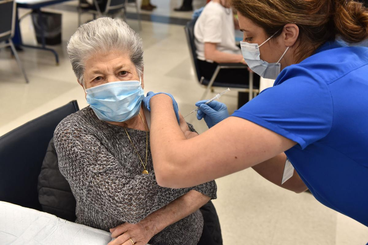 Rosemarie Jarrett, RN, of Westerly Hospital, right, adminsters a dose of vaccine at the Westerly Senior Center.jpg