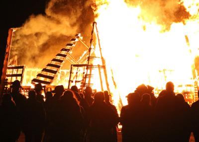 Folks gather around to watch the deteriorating structure of the 2019 New Years Eve Bonfire on Tuesday evening, December 31, 2019, in Ninigret Park, Charlestown, RI. | Jackie Turner, Special to The Sun.