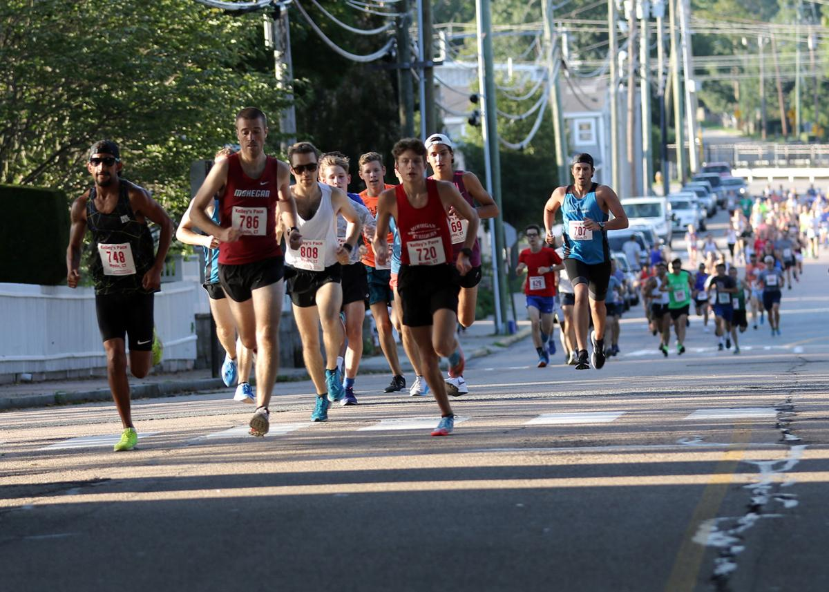 "Runners make their way along Water Street in the first lap of the ""Battle of Stonington 5k"" foot race, held Tuesday, August 20th, 2019 in Stonington Borough. The event is now in its 21st year. 