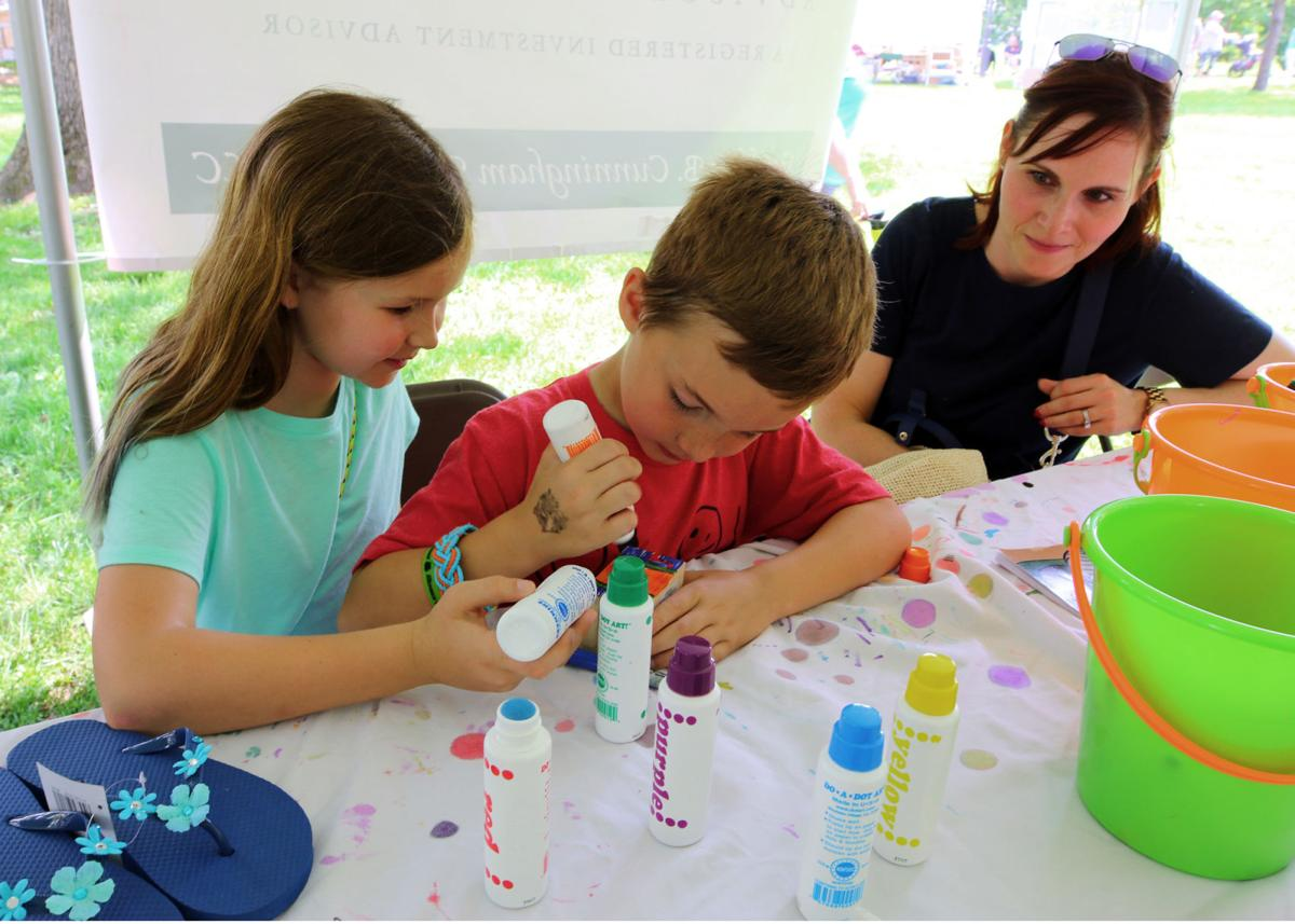 The arts and crafts tent at the 22nd Annual Virtu Art Festival, held in Westerly's Wilcox park, was a fun place Saturday for children and adults alike. Here Fallan and Donovan Torbett work diligently on their art work as mom Jennifer looks on.   Jackie Turner, Special to The Sun.