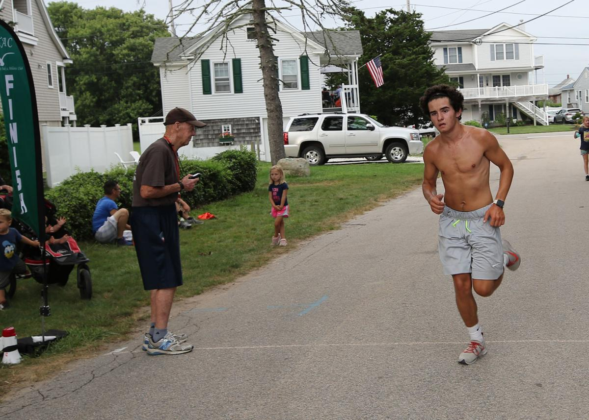 Nick Turo, first place finisher and over-all winner of the 5k event, crosses the finish line at 17:16 in the final regular-season race of the Tom McCoy Family Fun Run series, held Wednesday evening, August 7th, 2019 in Misquamicut. | Jackie L. Turner, Special to The Sun.