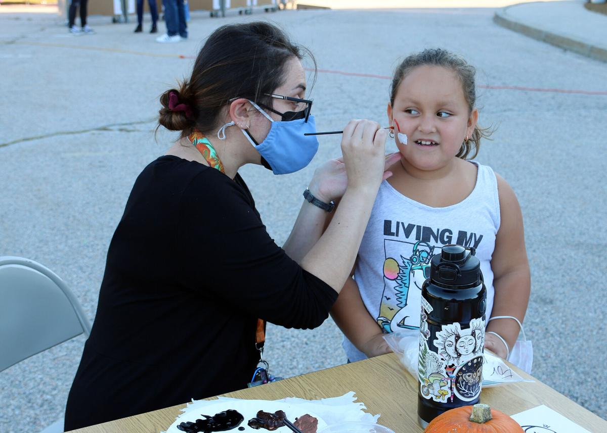 Art teacher Meghan Riley paints a brightly colored rainbow on the cheek of first grader Lily Valdez. Springbrook Elementary School First Annual Fall Fest. Thursday, October 7, 2021, Springbrook Elementary School, Westerly, RI.   Karen Stellmaker, Special to The Sun.