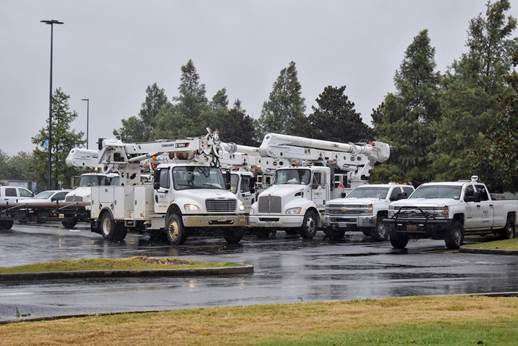 Utility trucks stand by, prepared to restore power if needed after the storm.