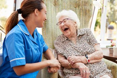 Older Woman Laughing With Aide