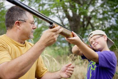 Dad and Son Learning How To Shoot A Gun