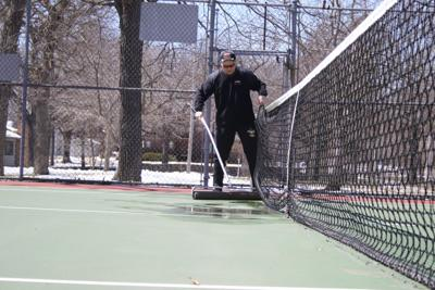 Rolling the tennis courts