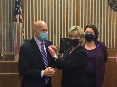 Joan Berry pins purple ribbon to lapel of District Attorney General Barry Staubus