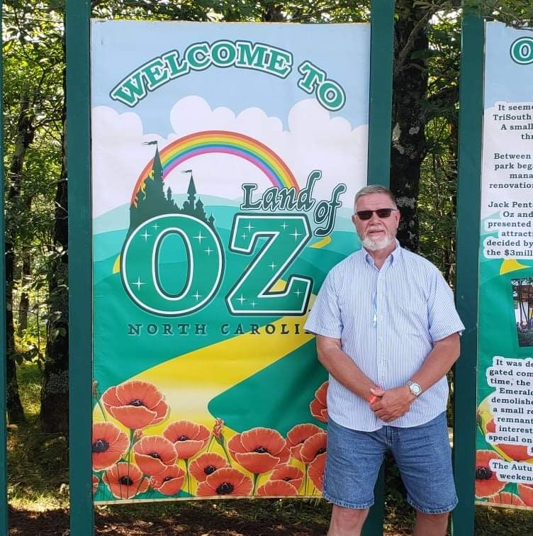 Kevin Davis with banners marking the entrance to the mountaintop Land of Oz
