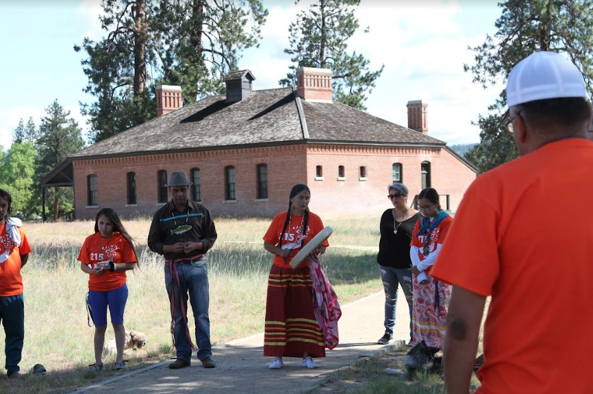 Colville tribal member Shelly Boyd, in the center with her hand drum, sings an honor song, June 15, for the paddlers outside the Fort Spokane guard house that once held tribal children who tried to escape the boarding school