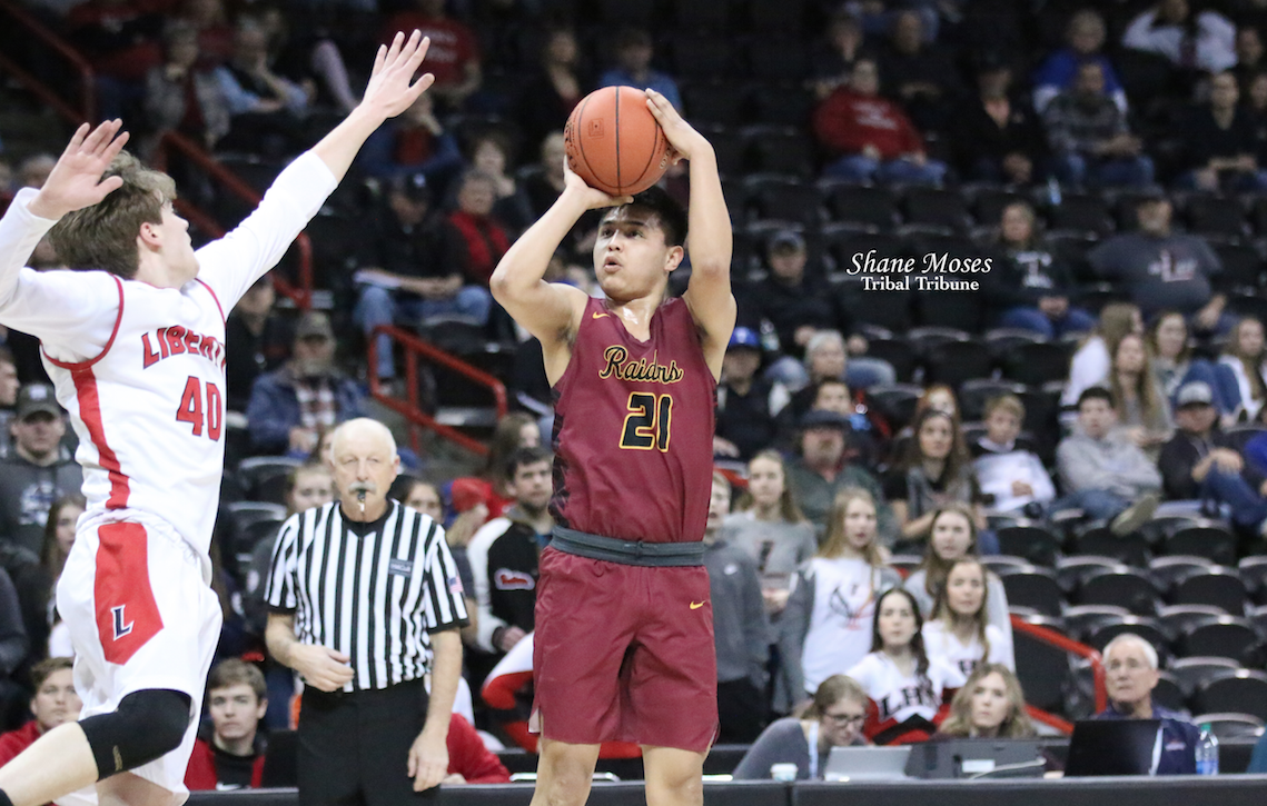 Colville tribal member Adam George (#21 red) shoots over Liberty's Van Ricker (#40 white) on Friday (March 6) afternoon in the WIAA 2B boys basketball state tournament.