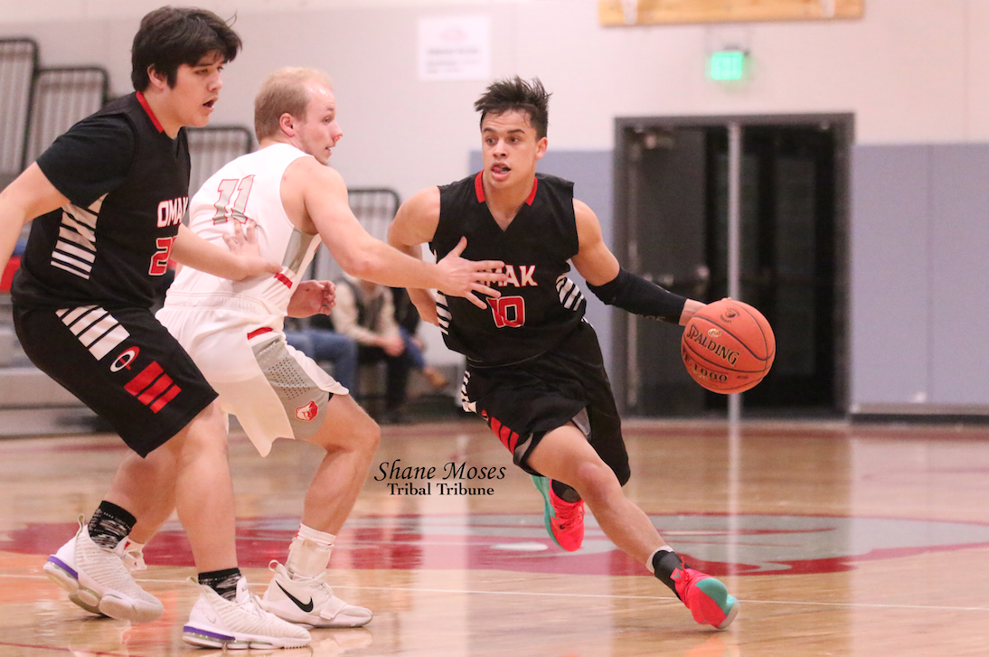 Colville tribal member Jaren Boyd (#10 black) of Omak drives to the hoop against Cascade on Friday (Jan. 17) evening in Caribou Trail League action. Omak won 63-30.