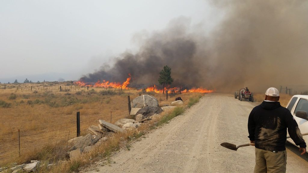 Tony Boyd watches a fire blaze out of control in the Omak countryside