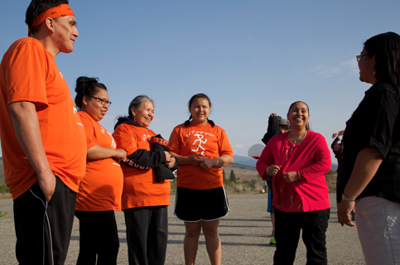 Keller Condon, Angelina Spencer, Pam Nanamkin, Shundina Spencer, Deby Stanger and Sharey Redthunder visit before stretching. Last year, the Unity Run's first year across the international border, Pam carried the honorary feather.