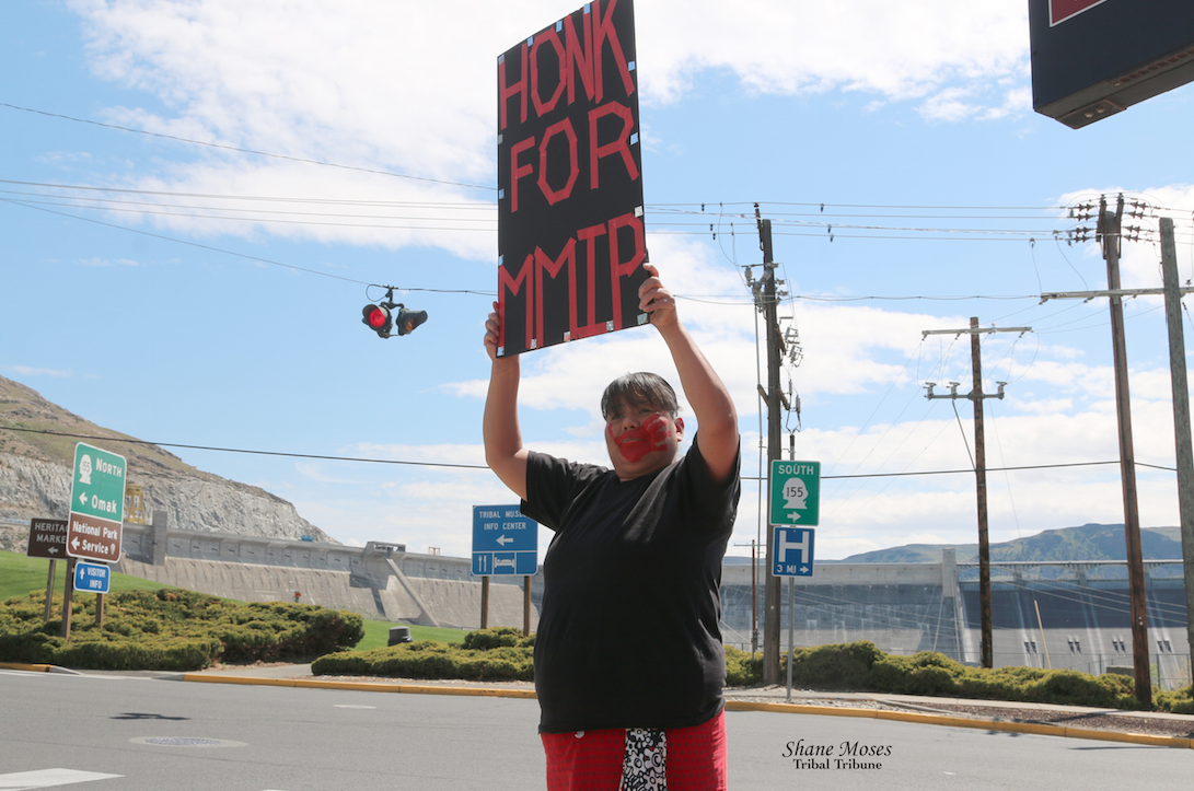 Colville tribal member Deanna James holds a MMIP sign in Coulee Dam, May 5