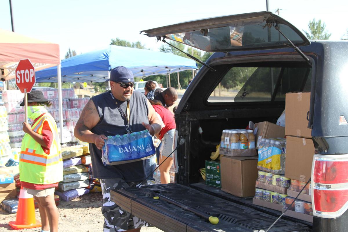 Colville tribal member Brian Peterson helps unload cases of water and food on July 21st