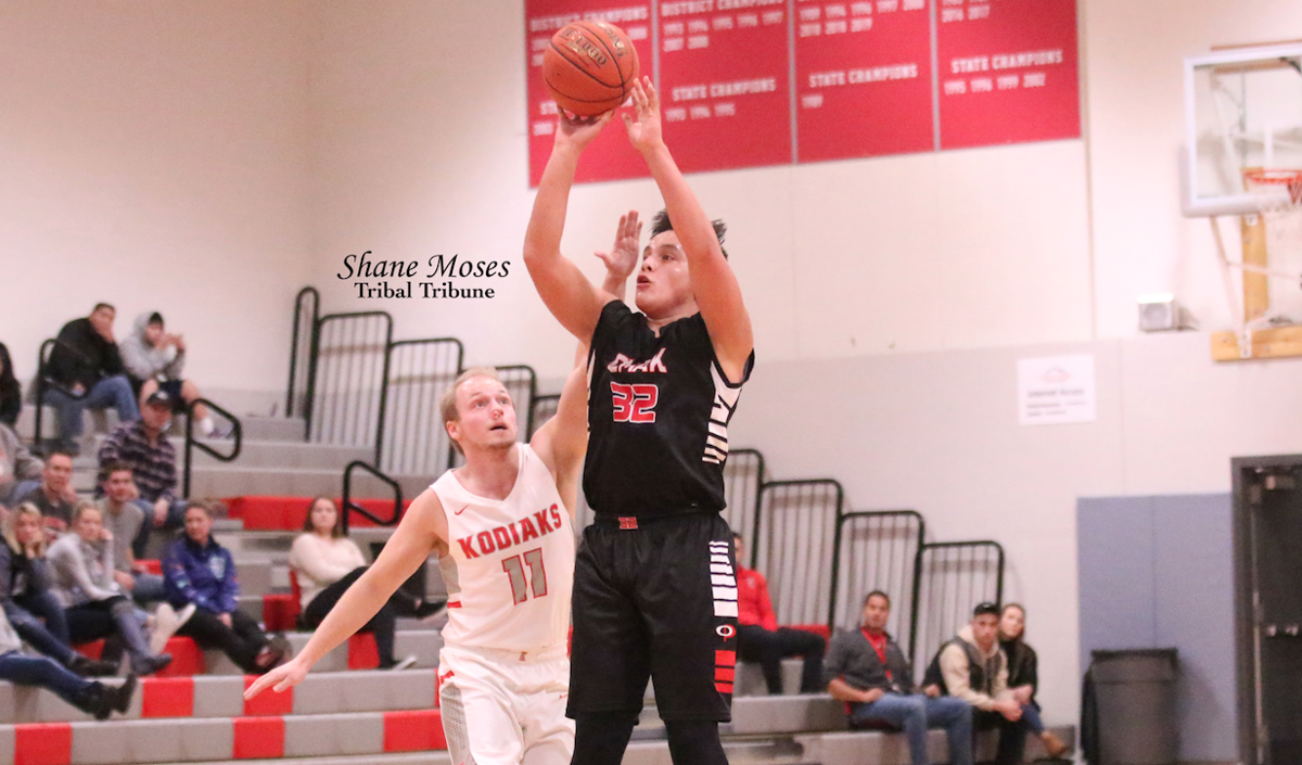 Colville tribal member Tre Marchand (#32 black) of Omak shoots over Cascade's Teague Duncan on Friday (Jan. 17) evening in Caribou Trail League action. Omak won 63-30.