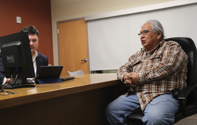 Colville Tribal elder Ernie Brooks and Lance Brender, U.S. military staff college, study the conjugations of different verbs in the Moses-Columbian language as part of their effort to record verbs for preservation of the language.