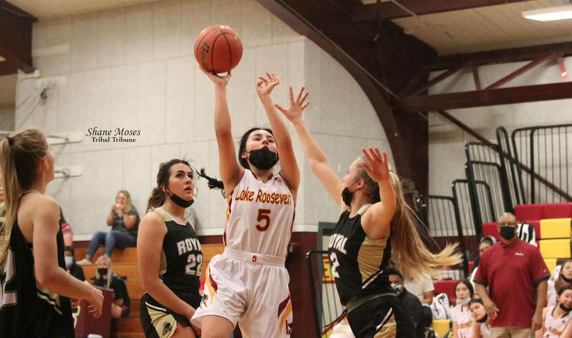 Colville tribal member Shyanne Marchand (#5 white) of Lake Roosevelt attacks the paint and goes up for a shot against Royal (June 14)