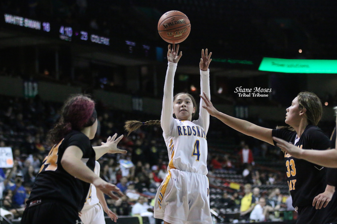 Colville tribal member Ashlynn Hill (#4 white) of Wellpinit gets a shot up against Clallam Bay on Wednesday (March 4) afternoon in this year's WIAA 1B girls state basketball tournament. Hill averaged 16.25 points per game in four state games.