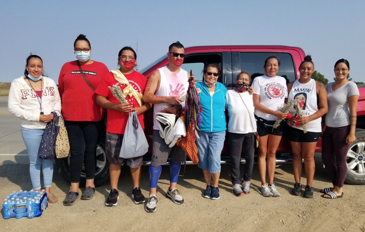 Ethan LaDeaux and Willi Bessette, third and fourth from left, stand with a number of runners on the Rosebud Sioux Reservation during their run across America last summer.