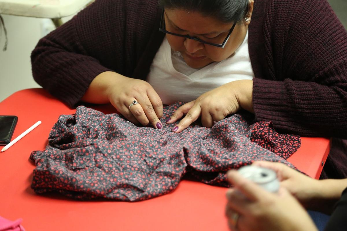 Chantel Hill, Crow Tribe, works on her skirt in Airway Heights, Friday.