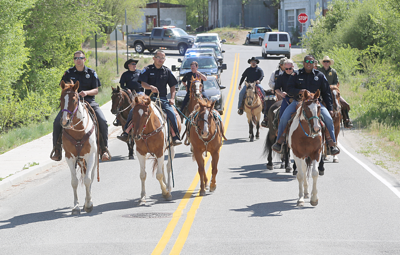 Colville Tribal Natural Resource Enforcement officers Neal Johnson, left, Rocky Timentwa, center, and Victor Landeros lead the group of horse riders across the Nespelem School Loop Road Bridge during a ride honoring fallen officers. Timentwa led a riderless horse in honor of past NRE officer Hunter Mason, who died while off duty.