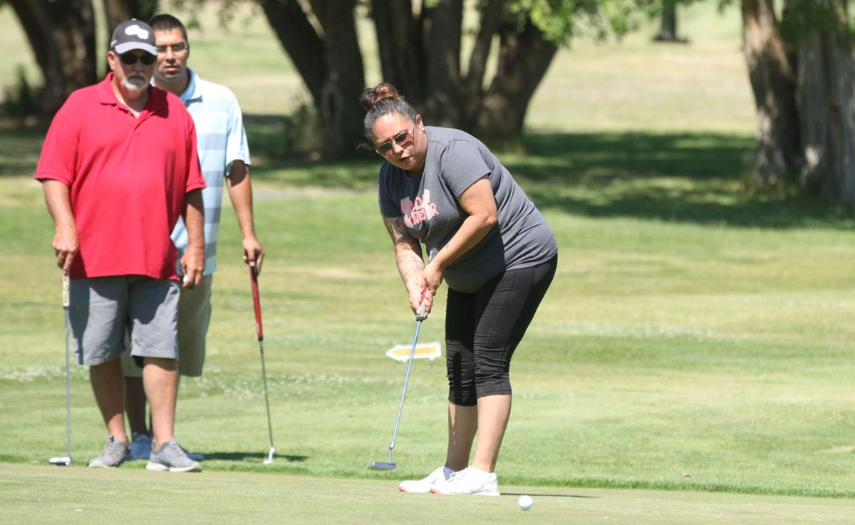 Colville tribal member Rena Whiteman putts a shot at the Coyote Open Golf Tournament on Saturday afternoon (July 14) at Banks Lake Golf Course