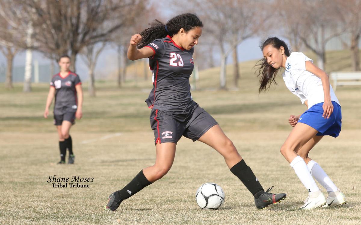 Colville tribal member Danielle Sparks (#23 grey) of Okanogan dribbles around Tonasket defenders on Thursday (April 1) evening in Central Washington 2B League action. Okanogan won 7-0