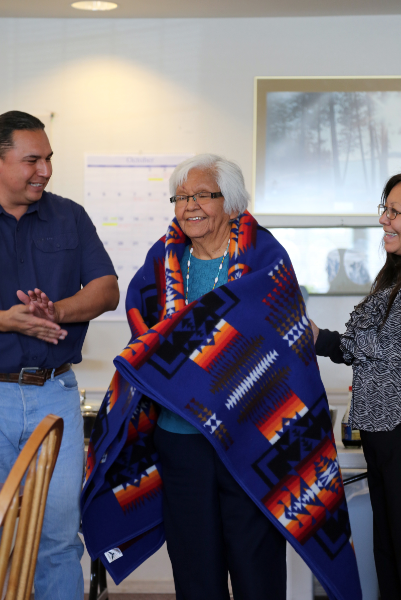 Ricky Gabriel, CBC, and Peggy Circle present Tribal elder Joanne Leith with an honorary Pendleton at her retirement luncheon, Oct. 5
