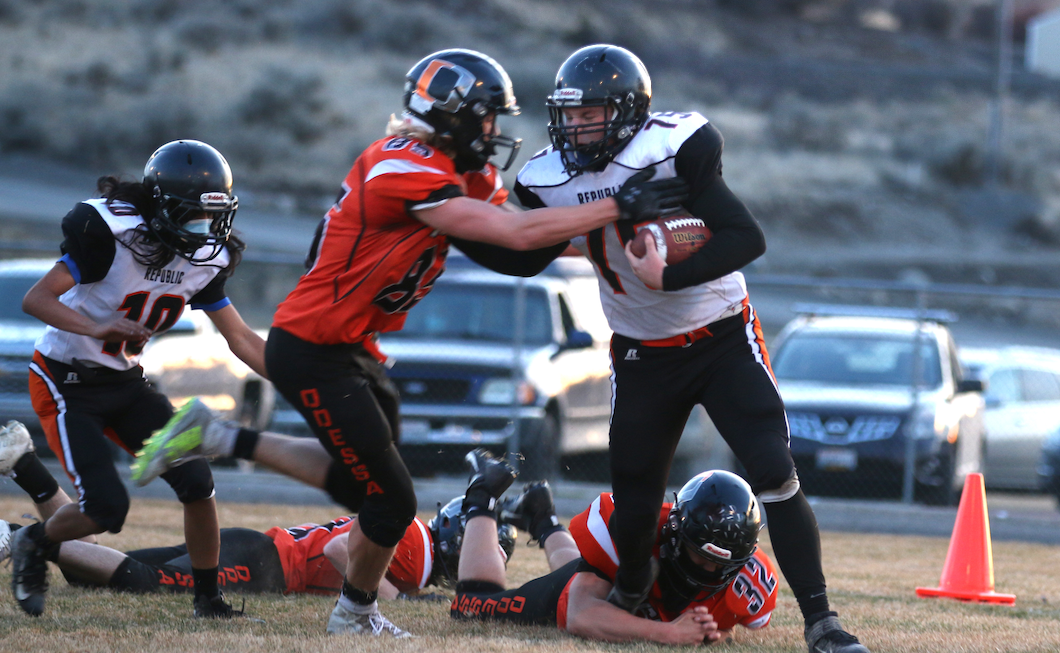 Colville tribal descendant Trace Fletcher #75 white for Republic gets the hand off and runs forward against Odessa on Saturday night in the NE 1B League Championship game. Odessa would go on to win 78-0.