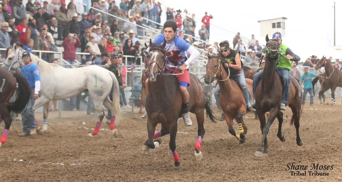 Colville tribal member Matthew Pakootas Jr. (blue), jockey for Northwest Express jumps out to the lead ahead of fellow tribal members Oliver Pakootas, jockey for Grizzly Mountain, and Terrance Holford, jockey for Arrow Lakes Express in the senior Indian Relay championship race on the final day of the North Central Washington Fair in Waterville, WA on Sunday, August 26