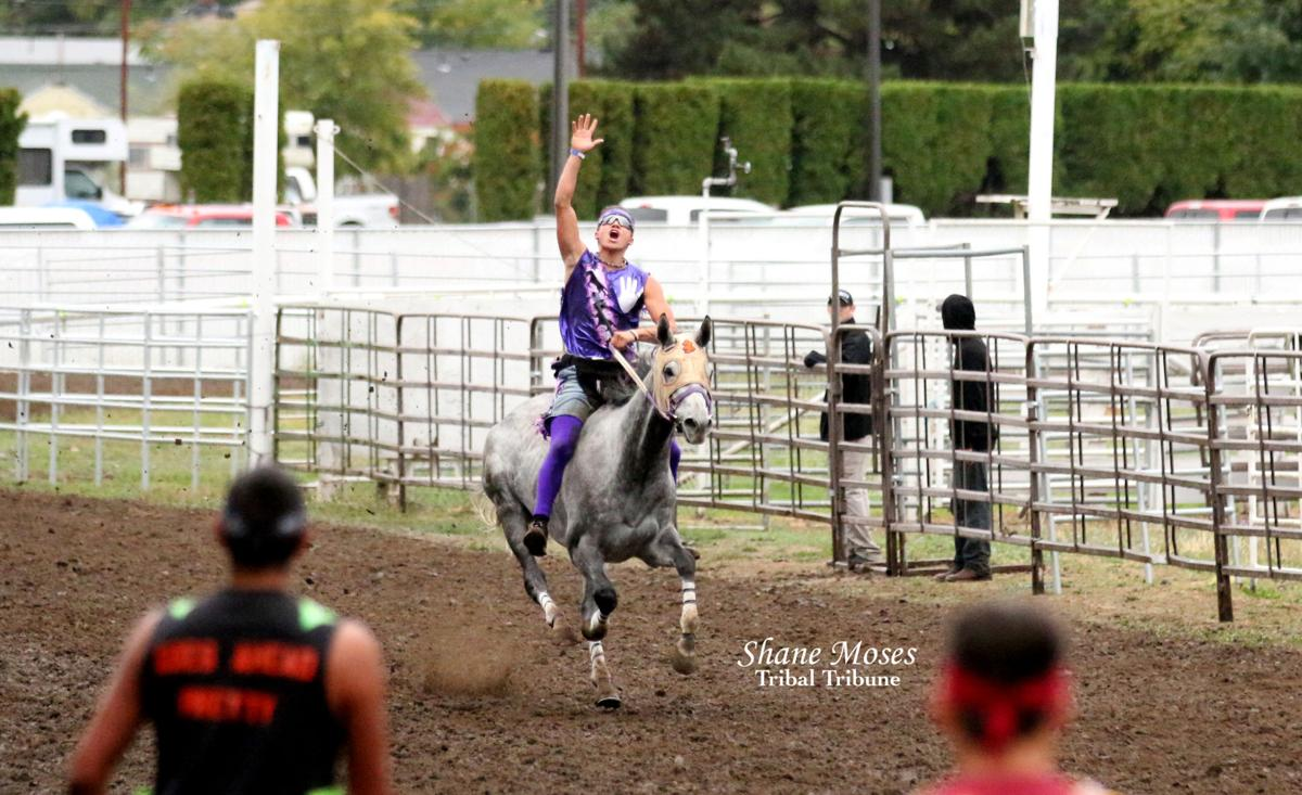 Scott Abrahamson (Purple), jockey for Abrahamson Relay, raises his hand in trimuph as he crosses the finish line of this year's Indian Relay Championship on Sunday at the Walla Walla County Fairgrounds