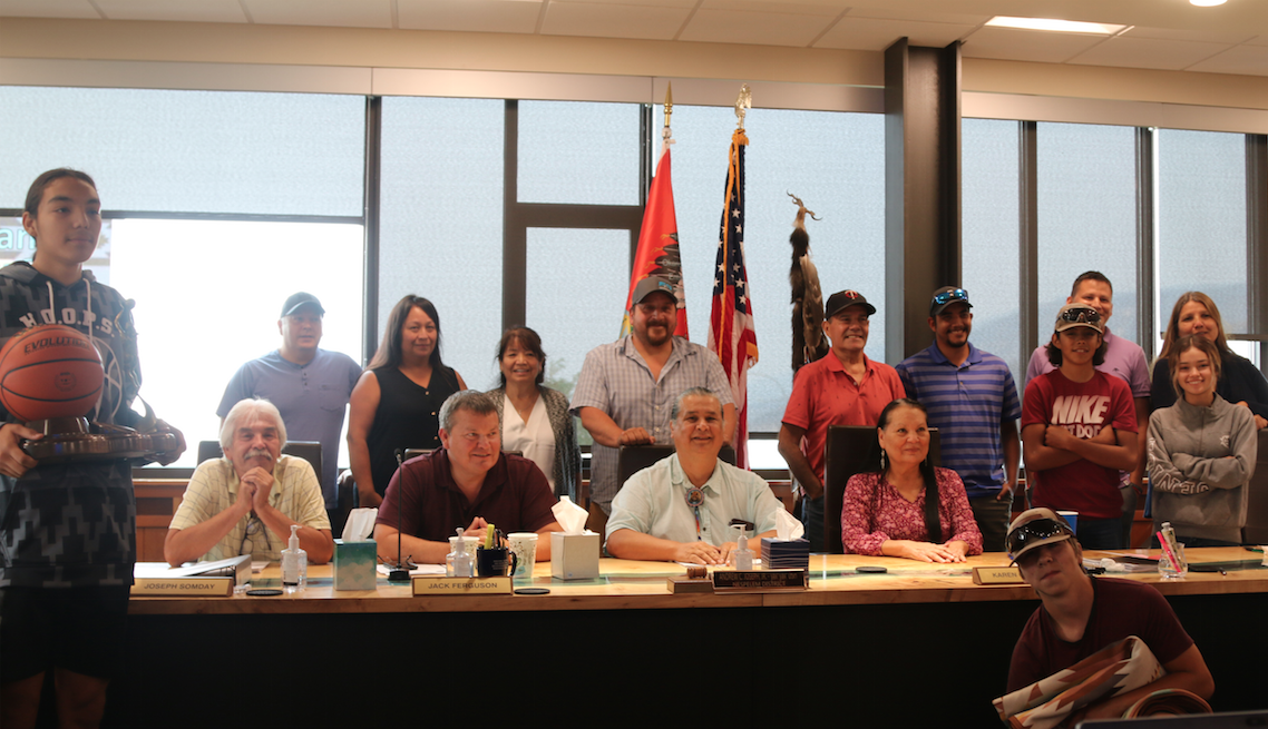 To the far left, Alonzo Adams holds the NABI Tournament championship trophy and to the right and Tito Pakootas kneels in front of the Council Table as both Colville youth were acknowledged for their recent success on Monday (Aug. 2) afternoon in Council Chambers before members of the Colville Confederated Tribes Business Council