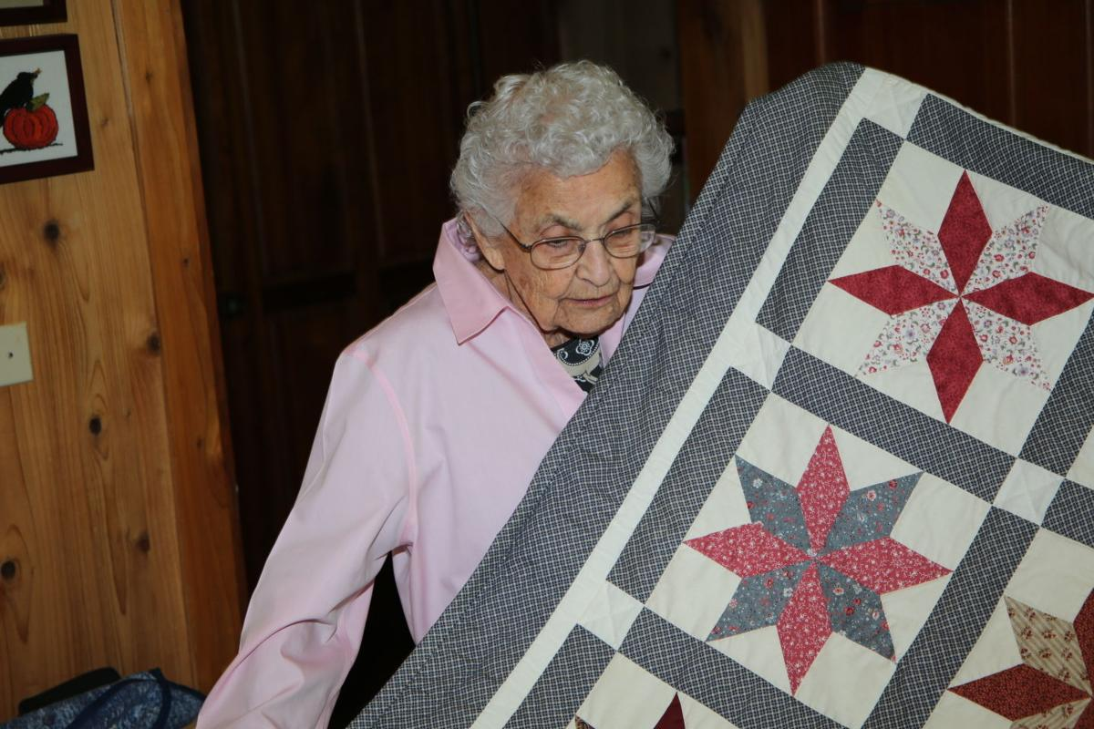 Wilda Watts unfolds a quilt she made