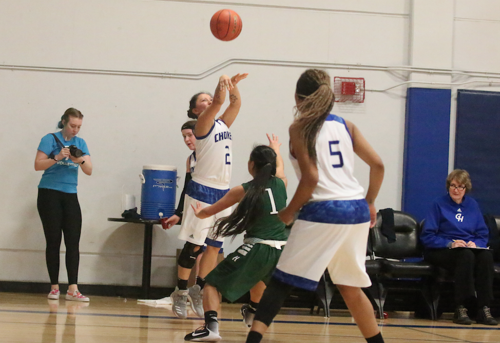 Colville tribal member Katie Brisbois of Grays Harbor College lets it reign as she buries a 3-point shot against Highline's Jahnna Kahele-Mad on Feb. 15 at Aberdeen in Northwest Athletic Conference action