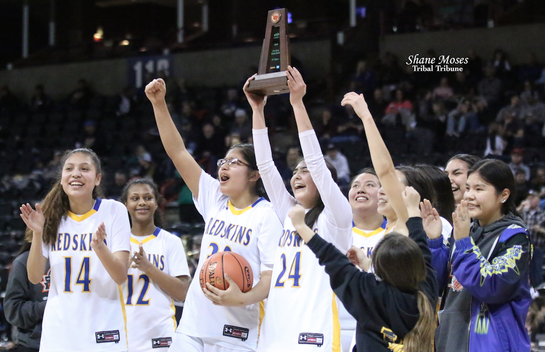 Colville tribal member Lachelle Boyd (#24 white) of Wellpinit holds up this year's WIAA 1B girls 4th place trophy. The Lady Redskins beat Curlew 56-40 on Saturday (March 7) morning in the 4th/6th place game at this year's 1B girls state basketball tournament.