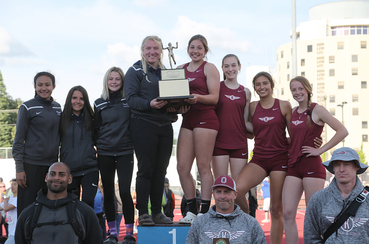 Colville tribal member Daniele Sparks, left, and tribal descendant Myra Rasmussen, second from right, stand with the Okanogan girls track and field team, celebrating their WIAA State 1A Track and Field Title, Saturday in Cheney.