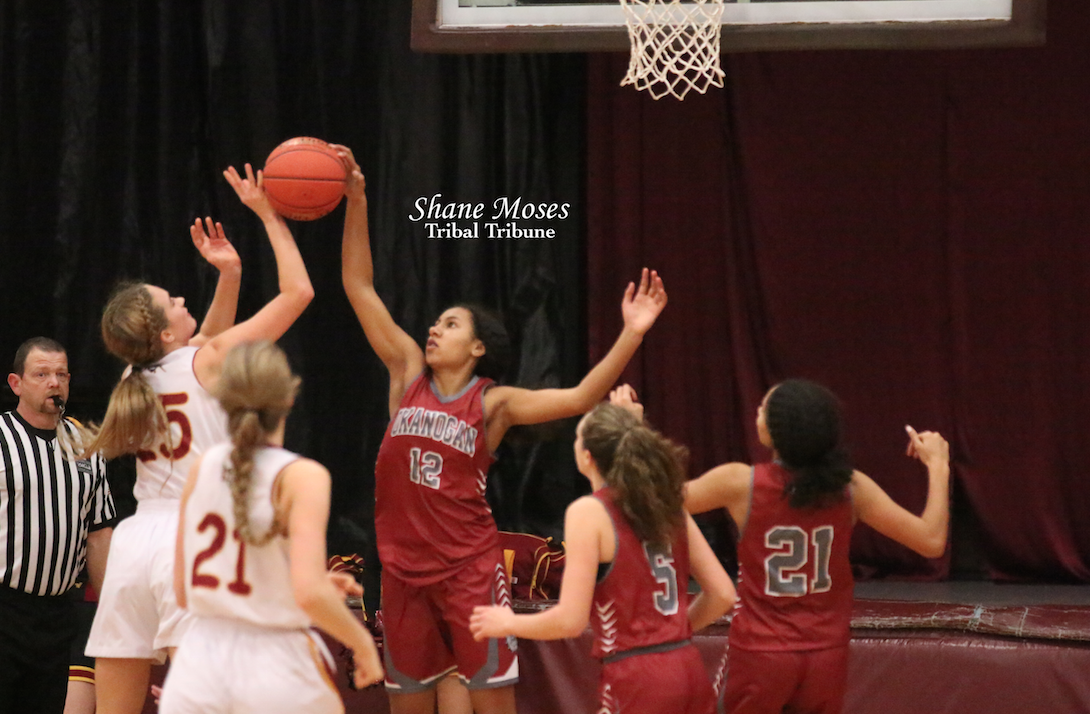 Okanogan's Sydney Sparks (#12 red) blocks the shot of Lake Roosevelt's Ellie Hansen (#25 white) on Tuesday (Jan. 21) evening in non-league action. Sparks a tribal member, helped Okanogan to a 57-34 win.