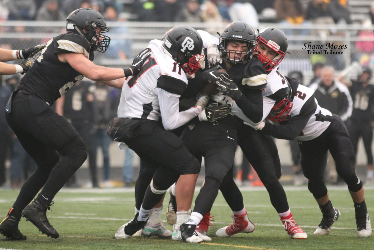 Anthony Cordona (#3 white), and Colville tribal member Tanner Hall (#11 white) of Omak bring down Royal's Lorenzo Myrick on Saturday afternoon in the quarterfinals of the WIAA 1A state playoffs