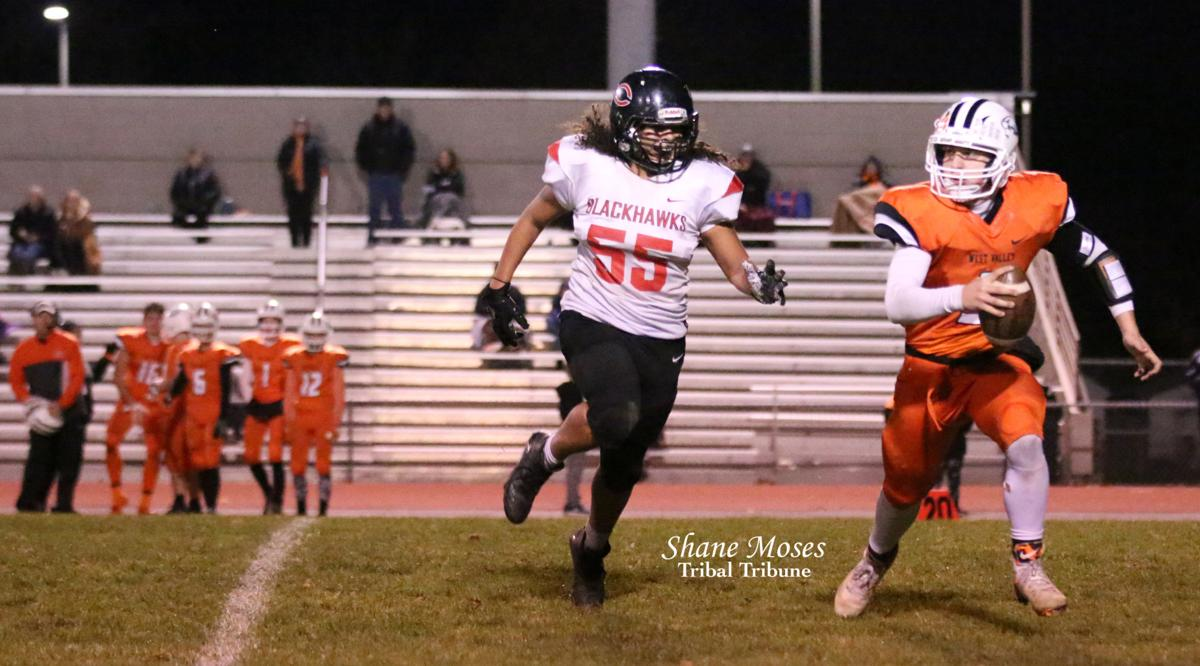 Eti Ena (#55 white) chases West Valley's quarterback on Friday night