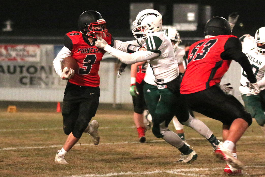 Colville tribal member Kessler Fjellman (#3 black) quarterback runs the ball against Chelan on Friday night in Caribou Trail League Action. Chelan would go on to win 29-6.