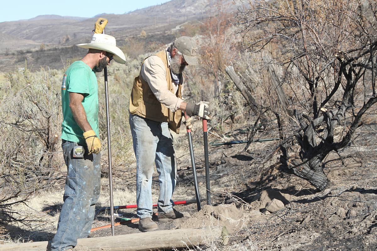 Volunteers Mark Tesch, right, and Dennis Hoots, left, rebuild fence near Highway 97, Tuesday, in an effort to help the community recover from the Cold Springs Fire that burned approximately 190,000 acres on the Colville Indian Reservation.