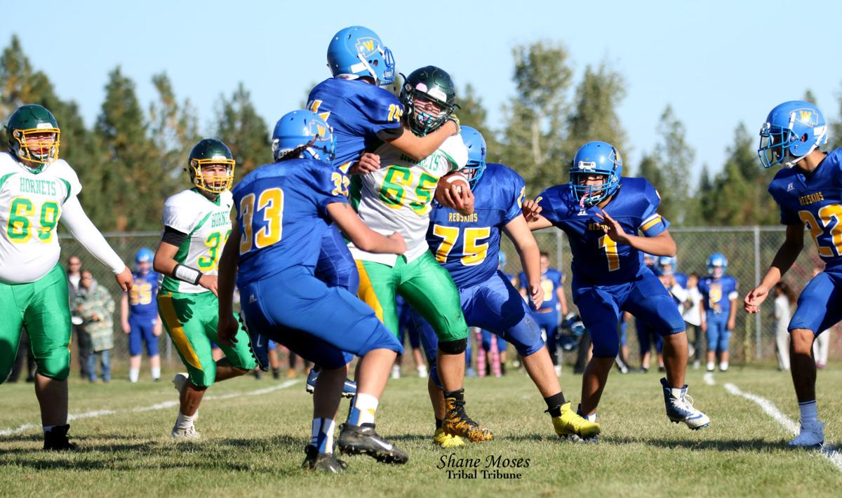 Colville tribal member Lonnie Simpson Jr. (#65 white) of Inchelium gets wrapped up by a handful of Wellpinit defenders on Friday (Oct. 11) afternoon