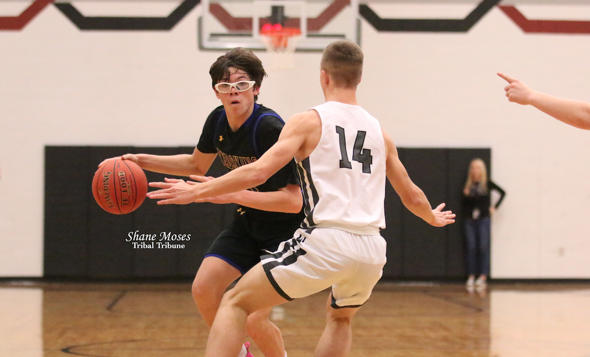Colville member Williams Dick IV (#11 black)of Wellpinit drives to the hoop against Parker Roberts (#14 white) of Almira Coulee Hartline on Feb. 1 in Coulee City. Dick would score eight points in the game.